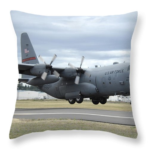 C-130 Throw Pillow featuring the photograph A C-130 Hercules Lands At Mcchord Air by Stocktrek Images