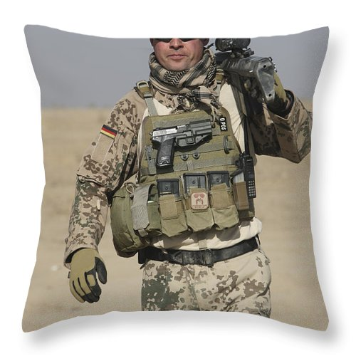 Weapon Throw Pillow featuring the photograph A German Soldier Carries A Barrett by Terry Moore