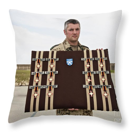 Afghanistan Throw Pillow featuring the photograph A German Soldier Holds A Display by Terry Moore