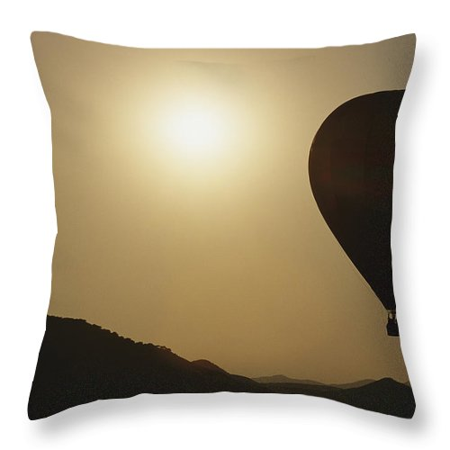 Scenes And Views Throw Pillow featuring the photograph A Hot Air Balloon Rises Above A Hilly by Raul Touzon