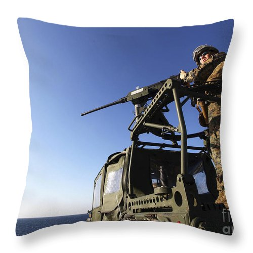 Camouflage Clothing Throw Pillow featuring the photograph A Machine Gunner Mounts A M-2 by Stocktrek Images
