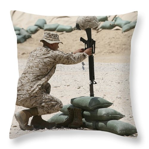 Military Throw Pillow featuring the photograph A Marine Hangs Dog Tags On The Rifle by Stocktrek Images