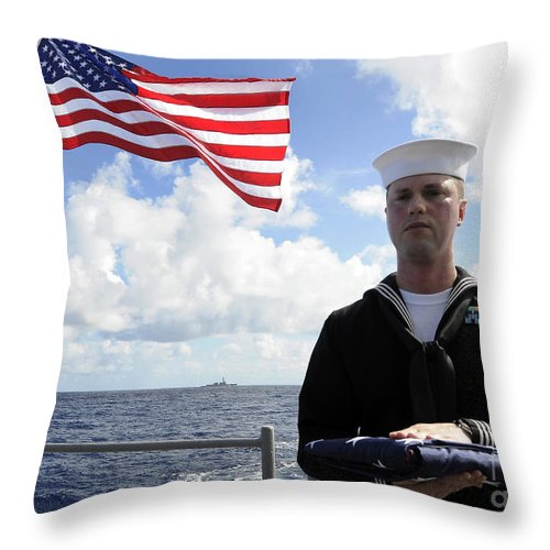Burial At Sea Throw Pillow featuring the photograph A Sailor Carries The National Ensign by Stocktrek Images