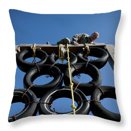 Clambering Throw Pillow featuring the photograph A Soldier Climbs Over A Tire Tower by Stocktrek Images