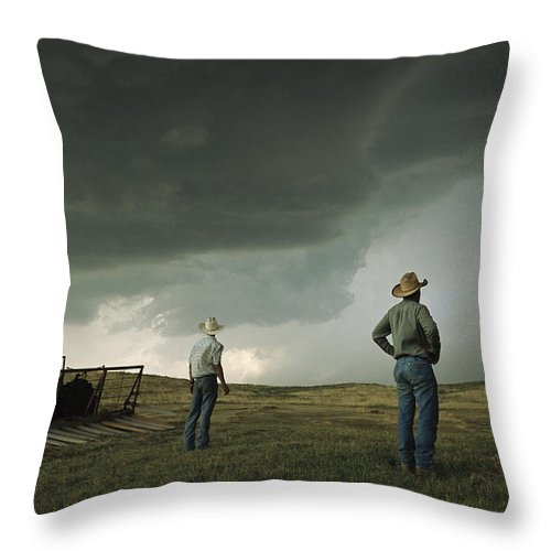 North America Throw Pillow featuring the photograph A Thunderstorm Halts Haying As Two by Jim Richardson