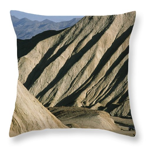 20-mule Team Canyon Throw Pillow featuring the photograph A Truck Is Dwarfed By Eroded Desert by Gordon Wiltsie