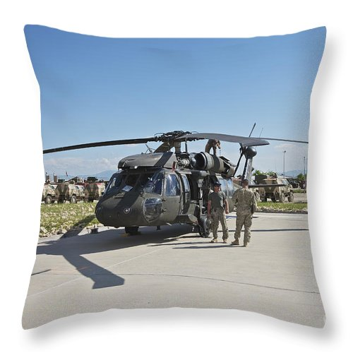 Operation Enduring Freedom Throw Pillow featuring the photograph A Uh-60l Blackhawk Parked On Its Pad by Terry Moore