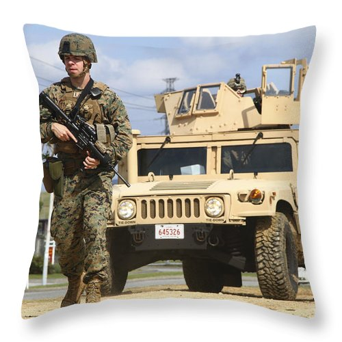 Motioning Throw Pillow featuring the photograph A U.s. Marine Guides A Humvee by Stocktrek Images