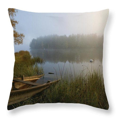 Europe Throw Pillow featuring the photograph A Weathered Rowboat On The Shore by Mattias Klum