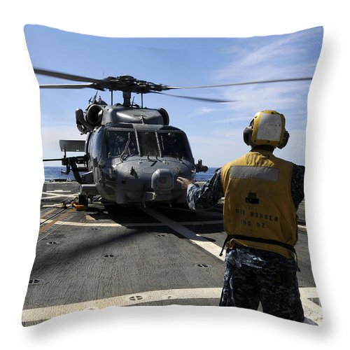 Operation Enduring Freedom Throw Pillow featuring the photograph Airman Signals To An Mh-60s Sea Hawk by Stocktrek Images