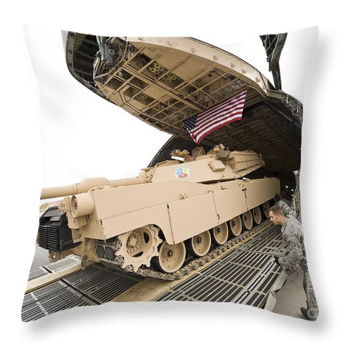 Tank Throw Pillow featuring the photograph Airmen Load A Tank Into A C-5m Super by Stocktrek Images