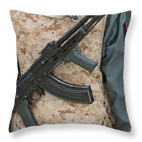 Gun Throw Pillow featuring the photograph An Ak-47 Rests On The Sling Of An by Terry Moore