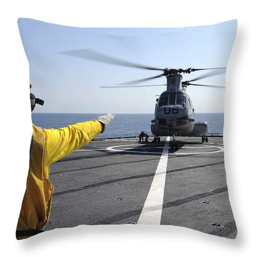Guidance Throw Pillow featuring the photograph Boatswain's Mate Directs A Ch-46 Sea by Stocktrek Images