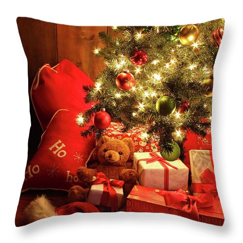 Background Throw Pillow featuring the photograph Brightly Lit Christmas Tree With Gifts by Sandra Cunningham