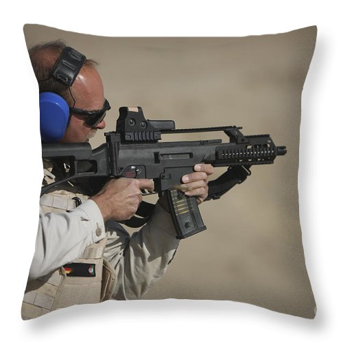 Isaf Throw Pillow featuring the photograph German Police, Isaf Member Fires A G36k by Terry Moore