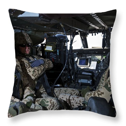 Cockpit Throw Pillow featuring the photograph German Soldiers Seated In A Uh-60l by Terry Moore