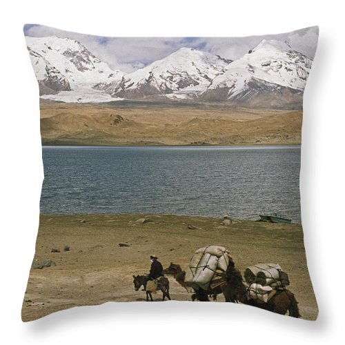 Camelus Bactrianus Throw Pillow featuring the photograph Kirghiz Nomad Leads Bactrian Camels by Gordon Wiltsie