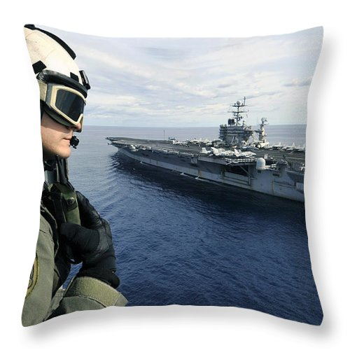 Aircraft Carrier Throw Pillow featuring the photograph Naval Air Crewman Conducts A Visual by Stocktrek Images