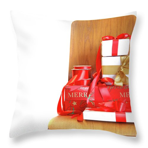 Chair Throw Pillow featuring the photograph Pile Of Gifts On Wooden Chair Against White by Sandra Cunningham