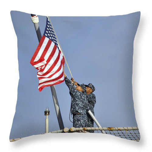Warship Throw Pillow featuring the photograph Sailors Lower The National Ensign by Stocktrek Images