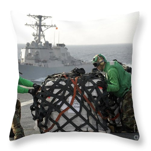 Color Image Throw Pillow featuring the photograph Sailors Move Supplies On The Flight by Stocktrek Images