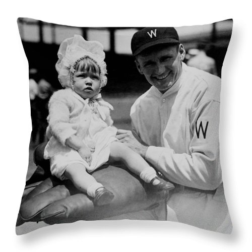 walter Johnson Throw Pillow featuring the photograph Walter Johnson Holding A Baby - C 1924 by International Images