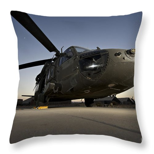 Isaf Throw Pillow featuring the photograph A Uh-60l Blackhawk Parked On Its Pad by Terry Moore