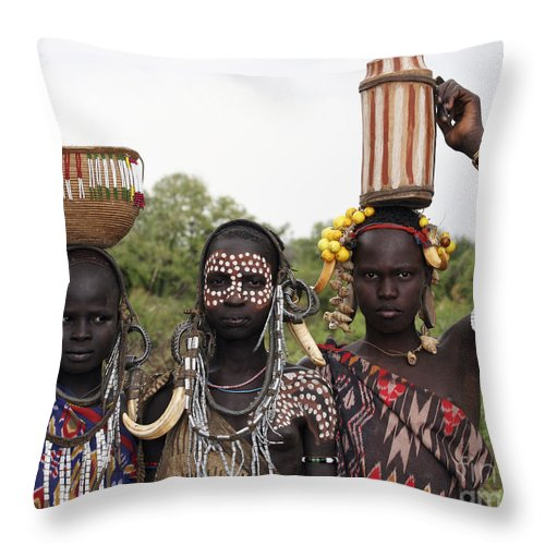 Ethiopia Throw Pillow featuring the photograph Mursi Tribesmen In Ethiopia by Gilad Flesch