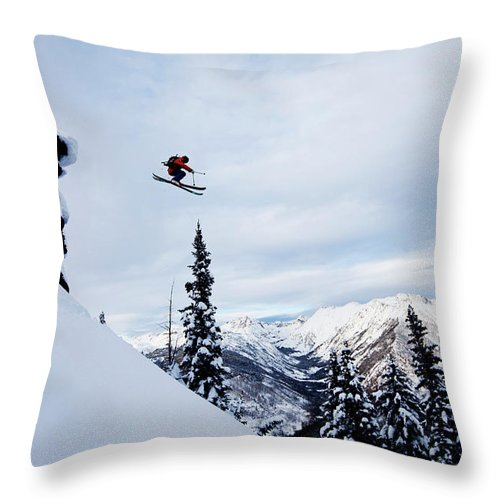 Skiing Throw Pillow featuring the photograph A Athletic Skier Jumping Off A Cliff In by Patrick Orton
