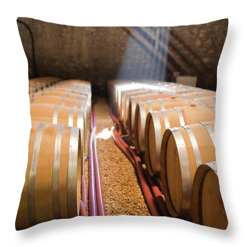 Alcohol Throw Pillow featuring the photograph Barrels In Wine Cellar by Johner Images