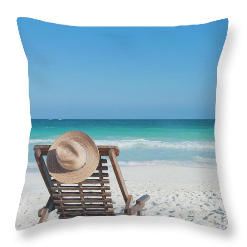 Scenics Throw Pillow featuring the photograph Beach Chair With A Hat On An Empty Beach by Sasha Weleber