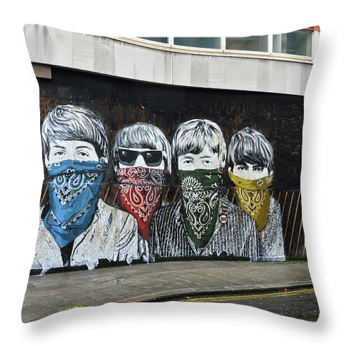 Bansky Throw Pillow featuring the photograph Yhe Beatles wearing face masks street mural in London by RicardMN Photography