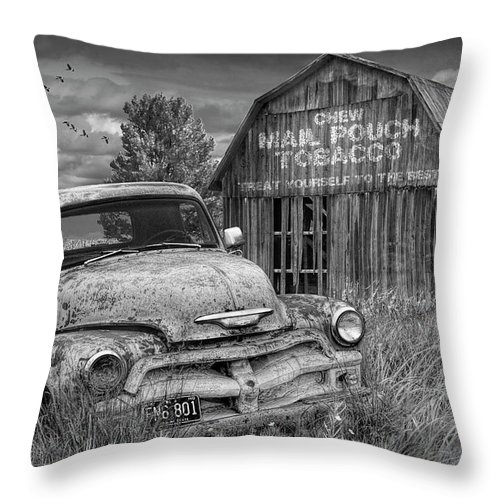 Chevy Throw Pillow featuring the photograph Black And White Of Rusted Chevy Pickup Truck In A Rural Landscape By A Mail Pouch Tobacco Barn by Randall Nyhof