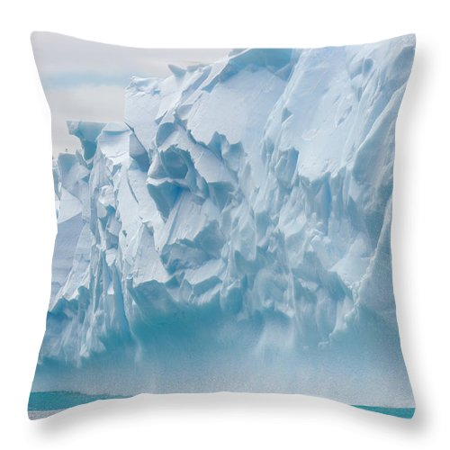 Scenics Throw Pillow featuring the photograph Blue Iceberg Carved By Waves Floats In by Eastcott Momatiuk
