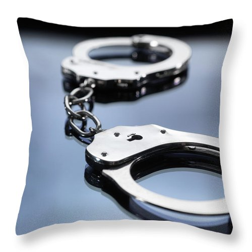 Punishment Throw Pillow featuring the photograph Close Up Of Metal Handcuffs by Andrew Brookes