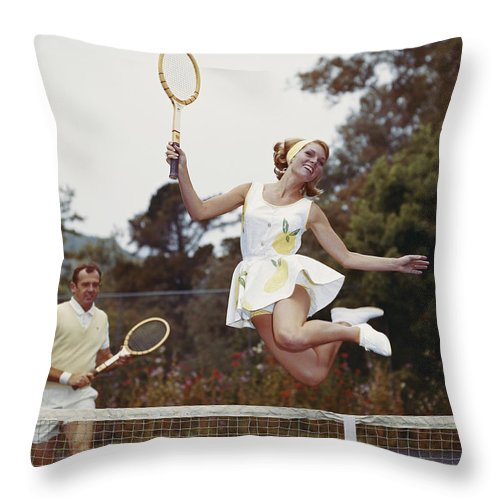 Heterosexual Couple Throw Pillow featuring the photograph Couple On Tennis Court, Woman Jumping by Tom Kelley Archive