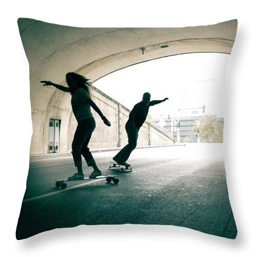 Mature Adult Throw Pillow featuring the photograph Couple Skateboarding Through Tunnel by Ian Logan