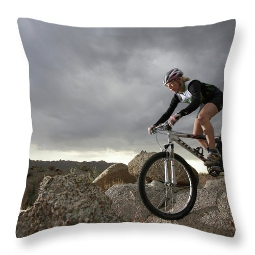 Sports Helmet Throw Pillow featuring the photograph Female Rider Mountain Biking Between by Thomas Northcut