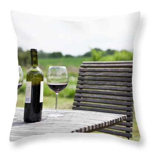 Five Objects Throw Pillow featuring the photograph Glasses And A Bottle Of Red Wine On An by Halfdark
