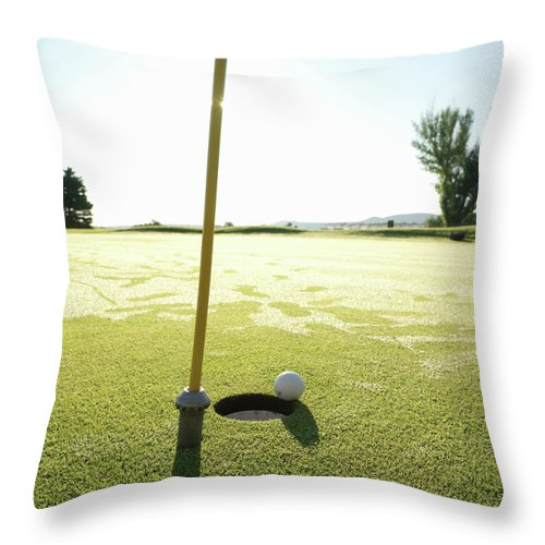 Grass Throw Pillow featuring the photograph Golf Ball Near Hole At Sunrise, High by Ascent/pks Media Inc.