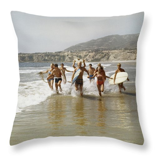 Young Men Throw Pillow featuring the photograph Group Of Surfers Running In Water With by Tom Kelley Archive