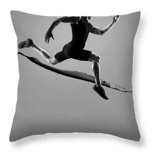 People Throw Pillow featuring the photograph Male Athlete Running Above Liquid Splash by Jonathan Knowles