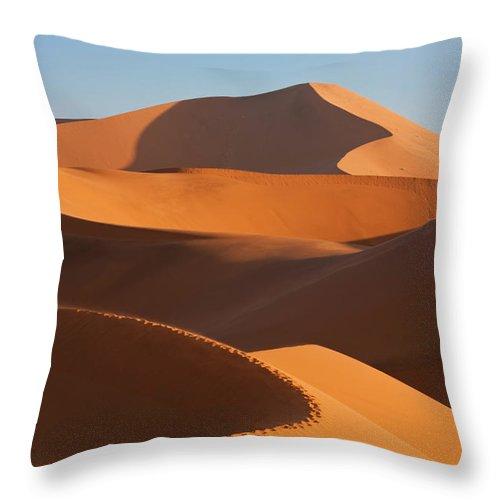 Shadow Throw Pillow featuring the photograph Man Climbing Sand Dunes, Namib Desert by Peter Adams