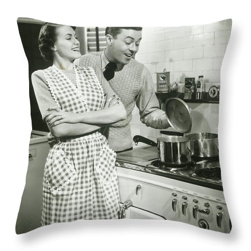 Heterosexual Couple Throw Pillow featuring the photograph Man Looking Into Pot In Domestic by George Marks