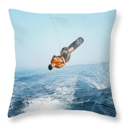 One Man Only Throw Pillow featuring the photograph Man Performing Wakeboarding Stunt At Sea by Paul Bradbury