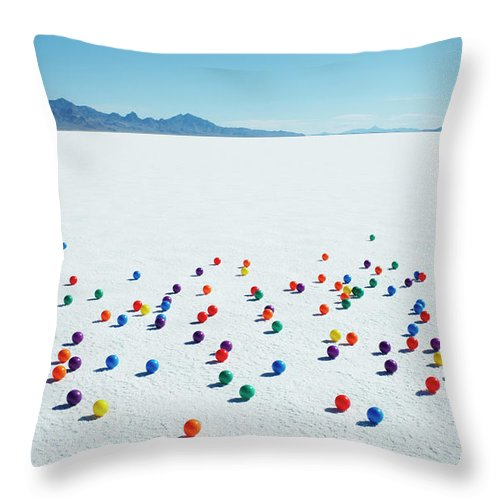 Out Of Context Throw Pillow featuring the photograph Multi-colored Balls On Salt Flats by Andy Ryan