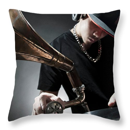 Youth Culture Throw Pillow featuring the photograph Oriental Dj Using Old Gramophone To Mix by Justin Lambert