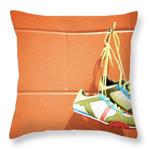 Hanging Throw Pillow featuring the photograph Runnig Shoes Hanging On A Hook by Pascalgenest
