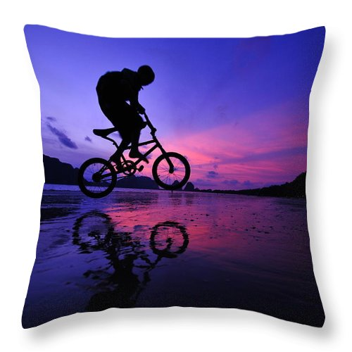 The Twilight Series Throw Pillow featuring the photograph Silhouette Of A Mountain Biker On Beach by Primeimages