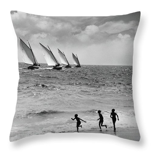 Following Throw Pillow featuring the photograph Three Boys Running Along Beach by Stockbyte